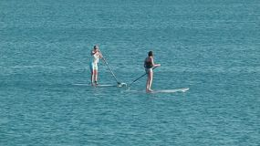 Two women passing by on stand up paddle boards off Cottesloe Beach in Perth, Western Australia.