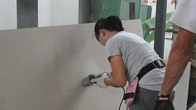 A female young adult on an overseas missions trip using a grinder on a construction project in the slums of Bangkok, Thailand.