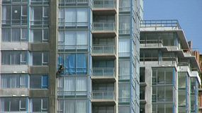 A building washer lowers himself down a level to continue washing a new high rise apartment building. (HD 1080p30)