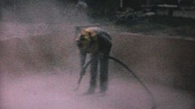 A construction worker sand blasts some concrete on a job site in 1967.