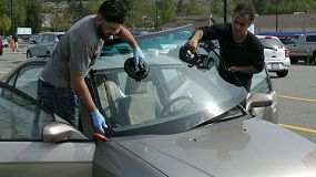 VANCOUVER, BC, CANADA, JUNE 2018: A professional auto glass installer replaces a damaged windshield with a brand new one in the parking lot of a shopping mall.