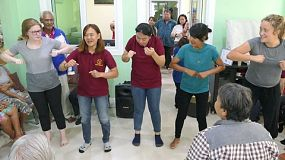 A group of young adults on a short-term missions trip spend time singing fun action songs with the elderly to encourage them in the slums of Bangkok, Thailand.