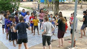 A group of young adults on a short-term overseas mission trip do a kids ministry program for kids living in the slums of Cambodia.