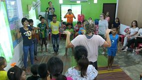 A group of young adults on a short term overseas missions trip have fun playing games with Thai children in the slums of Pattaya, Thailand.
