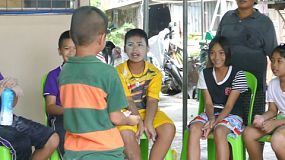 A group of young adults on a short term overseas missions trip have fun playing the baby powder game with Thai children in the slums of Pattaya, Thailand.