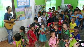 A group of young adults on a short term overseas missions trip have fun teaching action songs to Thai children in the slums of Pattaya, Thailand.