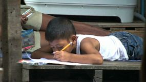 A young Thai boy diligently does his school homework in the slums of Bangkok, Thailand.