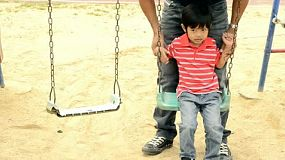 An Asian father and son playing together on a swing set, where the boy falls off the swing.