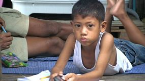 A cute young Thai boy plays with a cell phone instead of doing his school homework in the slums of Bangkok, Thailand.