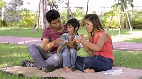 A Young Thai family spending time together in a park, teaching their son how to read.