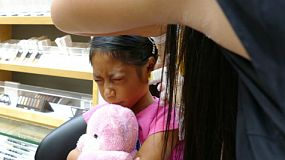 A cute little 9 year old Asian girl gets her ears pierced for the very first time.