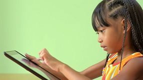 Profile view of a young Asian girl playing on a tablet pc.