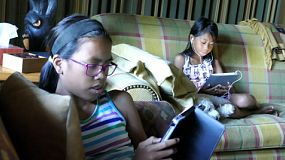 Two Asian sisters using their tablets in the living room while their faithful puppy rests on the sofa nearby.