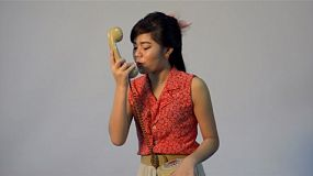 Vintage dressed young asian woman having a heated argument on the phone and hangs up - tracking shot.