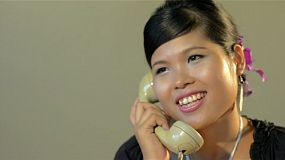 Vintage style set of young asian woman answering the phone - tracking shot.