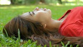 Young asian woman relaxing lying on the grass in a park.