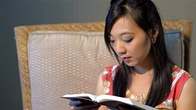 Young Asian woman relaxing on a chair, reading the bible/ a book.