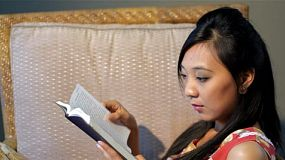 Young asian woman relaxing on a chair, while reading the bible or another book.