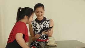Two young Asian women relaxing in a coffee shop, drinking tea, and sharing pictures on a tablet computer.