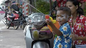 Bangkok, Thailand - April 14, 2014: A young boy with his family, shooting a water pistol while enjoying the water fights of the annual Songkran Festival in Thailand.