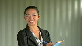 Young asian office worker turning and smiling at the camera.