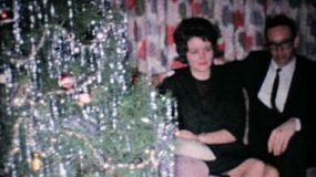 A young couple admires a festive poinsettia plant at Christmas 1962.