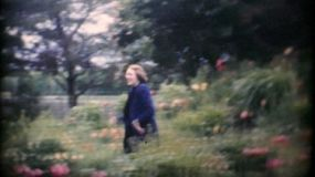 A pretty young female young adult enjoys wandering through a beautiful flower garden in 1967.