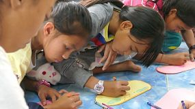 Young Asian girls in the slums diligently color their coloring sheet during an English class in Pattaya, Thailand.