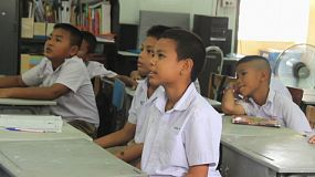 A class of young Asian male students repeat words being taught by their teaching during English class in Ratchaburi, Thailand.