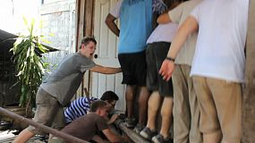 A group of young adults on an overseas missions trip work hard on a construction project in the slums of Bangkok, Thailand.