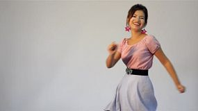 Young woman dressed in retro fashion having a great time dancing the twist.