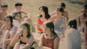 A group of young teenagers enjoy hanging out and eating a snack after swimming in the pool in 1969.