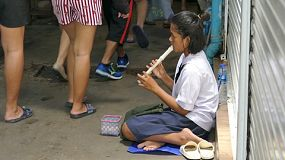 A young Asian teenage girl plays her recorder at the market in hopes of making money in Bangkok, Thailand.