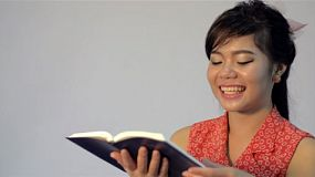 Young Asian woman bursts out laughing as she reads a book/the bible.