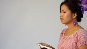 Young Asian woman thinking while reading a book/ the bible - dolly tracking shot.