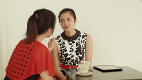 A young Asian woman consoling her sad and heartbroken friend over a cup of tea at a cafe.