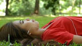 Young asian woman listening to music on her headphones, while relaxing lying on the grass in a park.