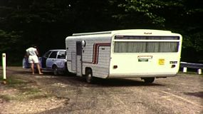 A young woman ready to get into their car and go on a trip with a caravan in tow in 1983.