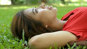 Young asian woman relaxing lying on the grass in a park, with her arms behind her head.
