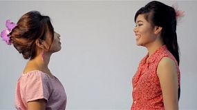 Two young Asian friends talking and laughing together - dolly in.