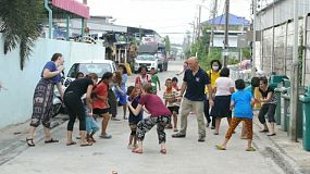 A group of cute Asian kids and a foreign youth missions team have fun playing tag in the slums of Bangkok, Thailand.