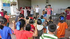 A group of high school students on an overseas missions trip singing action songs to kids in a hill tribe village in Chiang Rai, Thailand.
