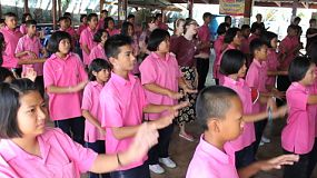 A group of cute Asian students and a foreign youth missions team have fun dancing during a school assembly in Ratchaburi, Thailand.