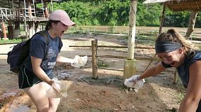 "CHIANG RAI, THAILAND, JULY 15, 2017: Two young adult girls on a short term overseas missions trip have fun playing ""Paddy Cake"" with elephant dung in Chiang Rai, Thailand."