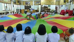 A group of young adults on a short term overseas missions trip have fun using a parachute with Thai children during English class in Ratchaburi, Thailand.