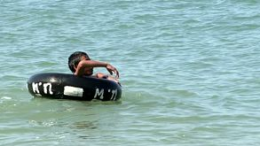 Asian Boy Playing With Inner Tube On The Ocean
