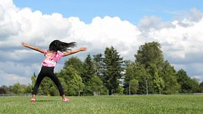 Cute Asian Girl Doing Cartwheels On The Grass